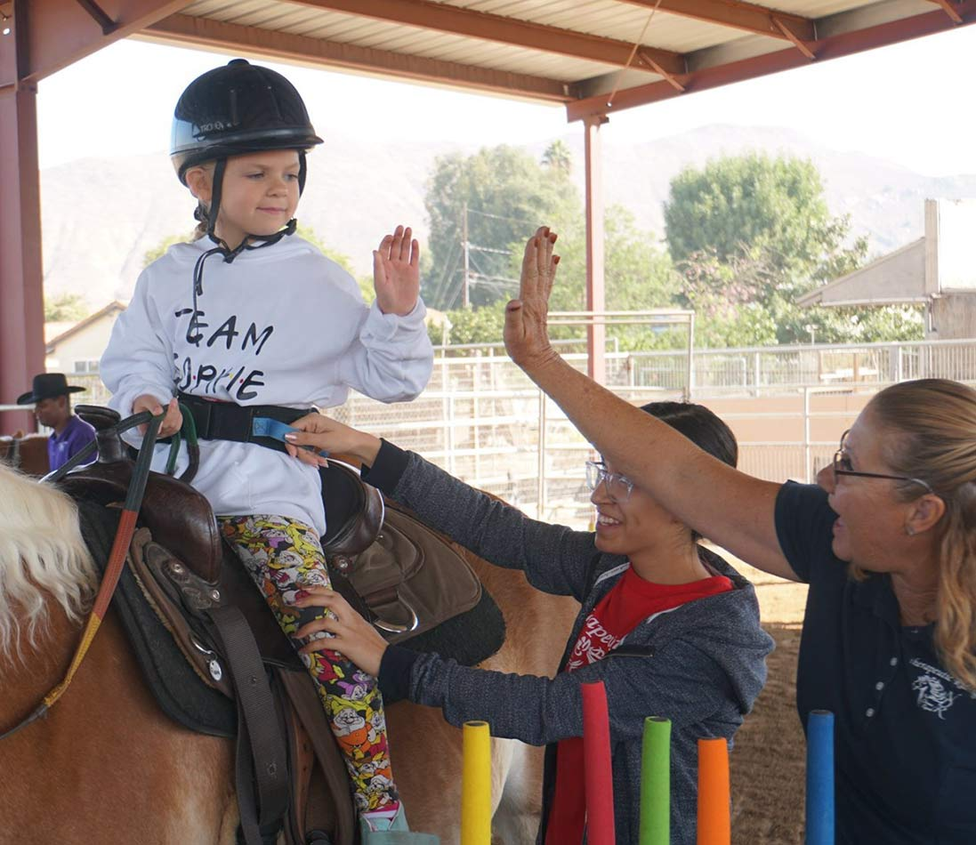 image: Young boy on a horse assisted with a belt and staff playing rings and giving Donna a high-five