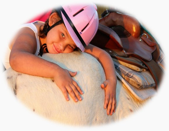 image: Young girl NDR participant laying her head on the back of a horse