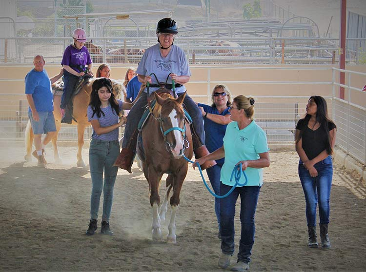 image: NDR team working with a participant on one of their horses